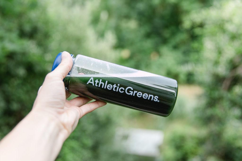 Athletic Greens Flasche in der Hand gehalten